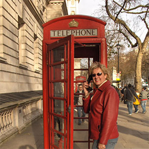 Kelly using a red phone booth